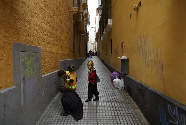 Children in fancy costumes play in a street during the Carnival of Cadiz, southern Spain February 15, 2015. (Photo by Marcelo del Pozo/Reuters)