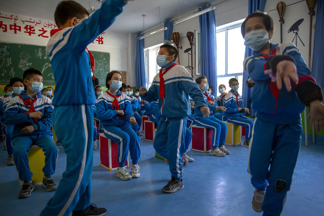Schoolchildren dance during a music class at a primary school in Awati Township in Kashgar in western China's Xinjiang Uyghur Autonomous Region, as seen during a government organized trip for foreign journalists, Monday, April 19, 2021. A human rights group is appealing to the United Nations to investigate allegations China's government is committing crimes against humanity in the Xinjiang region. Human Rights Watch cited reports of the mass detention of Muslims, a crackdown on religious practices and other measures against minorities in the northwestern region. (Photo by Mark Schiefelbein/AP Photo)