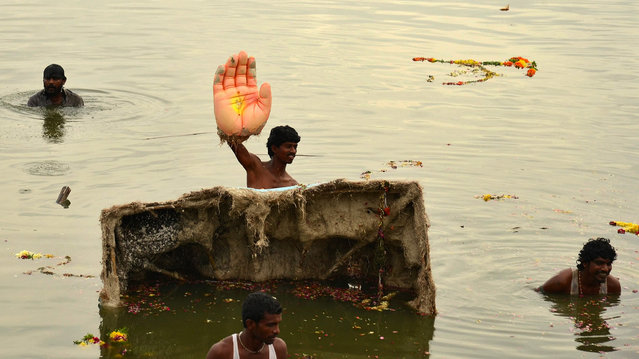 A man holds the hand of an idol of the Hindu elephant god Ganesh, the deity of prosperity, during idol immersion ceremony in the Hussain Sagar lake during the Ganesh Chaturthi festival in the southern Indian city of Hyderabad September 17, 2013. Ganesh idols are taken through the streets in a procession accompanied by dancing and singing and later immersed in a river or the sea symbolising a ritual seeing-off of his journey towards his abode, taking away with him the misfortunes of all mankind. (Photo by Krishnendu Halder/Reuters)