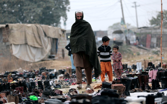 A customer looks at shoes for the winter with his children at a used shoe market in Islamabad, Pakistan November 22, 2016. (Photo by Caren Firouz/Reuters)