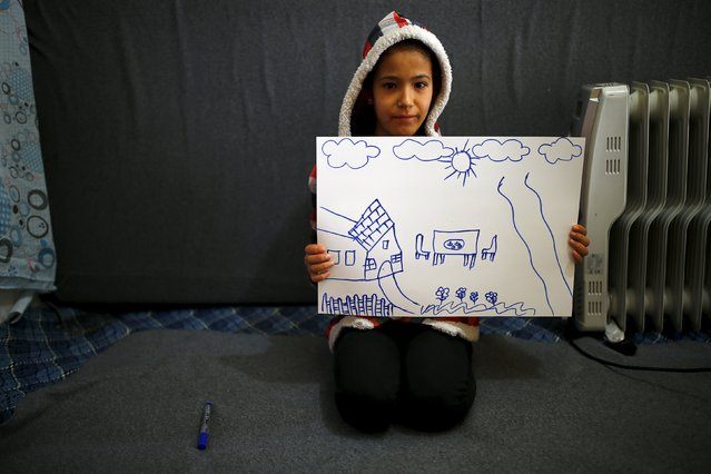 Syrian refugee Hale Selim, 13, shows her drawing of home in her tent in Yayladagi refugee camp in Hatay province near the Turkish-Syrian border, Turkey, December 16, 2015. (Photo by Umit Bektas/Reuters)