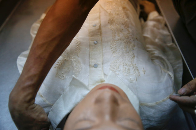 A funeral parlour worker dresses Florjohn Cruz after his autopsy at Eusebio Funeral Service in Manila, Philippines October 28, 2016. (Photo by Damir Sagolj/Reuters)