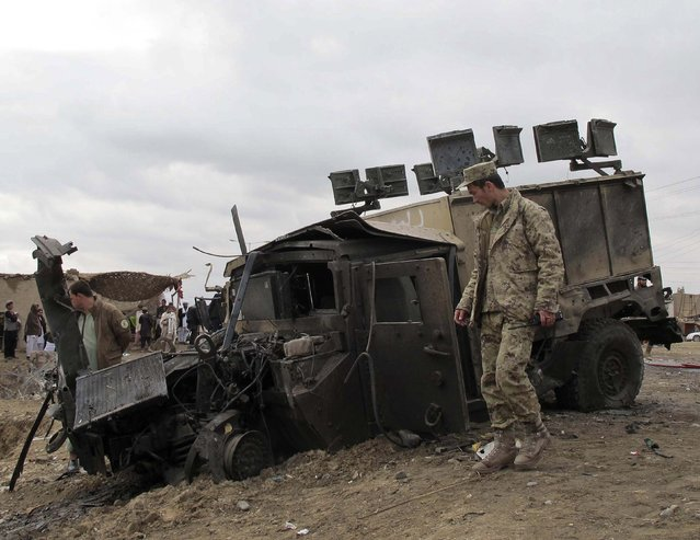 An Afghan policeman inspects the wreckage of a police armoured vehicle after a suicide attack in Helmand province January 22, 2015. (Photo by Reuters/Stringer)
