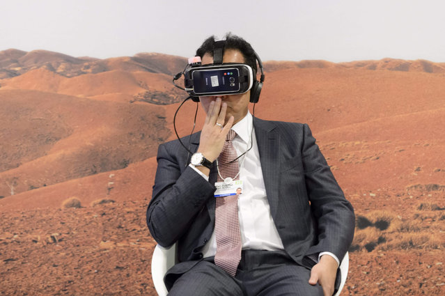 """A participant tries out virtual reality glasses while watching the world premiere of the virtual reality film """"Collisions"""" inside the Congress Center the first day of the 46th Annual Meeting of the World Economic Forum, WEF, in Davos, Switzerland, 20 January 2016. The overarching theme of the Meeting, which will take place from 20 to 23 January, is """"Mastering the Fourth Industrial Revolution"""". (Photo by Laurent Gillieron/EPA)"""