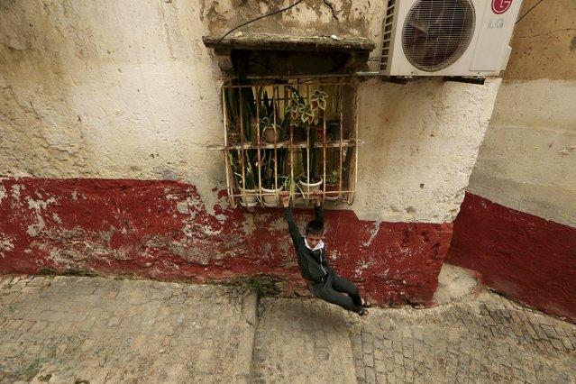 A boy swings on window bars in the old city of Algiers Al Casbah, Algeria December 3, 2015. (Photo by Zohra Bensemra/Reuters)