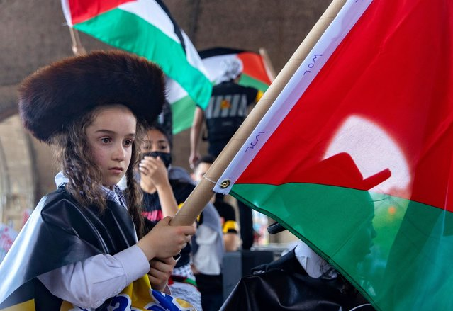A Jewish boy holding a Palestine flag takes part in a protest in support of Palestinians following a flare-up of Israeli-Palestinian violence, in the Queens borough of New York City, New York, U.S., May 22, 2021. (Photo by Jeenah Moon/Reuters)