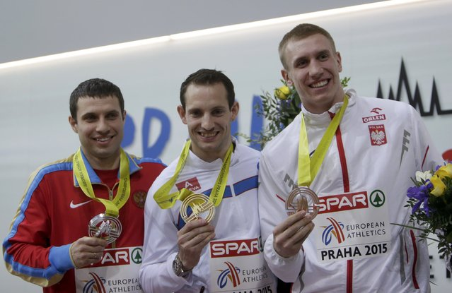 Winner Renaud Lavillenie, second placed Aleksandr Gripich of Russia (L) and third placed Piotr Lisek of Poland (R) celebrate on the podium at the medal ceremony for the men's pole vault final during the European Indoor Championships in Prague March 8, 2015. REUTERS/David W Cerny (CZECH REPUBLIC  - Tags: SPORT ATHLETICS)