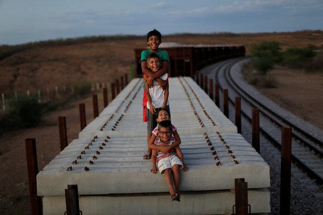Raniel da Silva, Ariel da Silva, Ariana da Silva and Daniel da Silva pose for a portrait on the top of a train wagon near the city of Salgueiro, Pernambuco state, northeastern Brazil, October 26, 2016. (Photo by Ueslei Marcelino/Reuters)