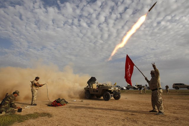 "Shi'ite fighters launch a rocket during clashes with Islamic State militants on the outskirts of al-Alam March 8, 2015. Thaier Al-Sudani: ""It was me and a few other Iraqi journalists working for local outlets. (Photo by Thaier Al-Sudani/Reuters)"