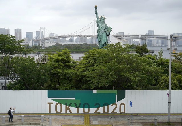 An advertising of Tokyo 2020 Olympic Games that have been postponed to 2021 due to the coronavirus disease (COVID-19) outbreak, is displayed near the Statue of Liberty replica with the Rainbow Bridge at the background, at the waterfront area of Odaiba Marine Park, in Tokyo, Japan on May 16, 2021. (Photo by Naoki Ogura/Reuters)
