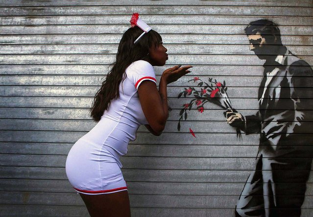 A dancer poses with a new installation of art by British graffiti artist Banksy painted on the front door of the Hustler Club in New York, October 24, 2013. Known for his anti-authoritarian black-and-white stenciled images, which have sold at auction for upwards of $2 million, the British street artist is treating New Yorkers to a daily dose of spray-painted art – while eluding the police and incurring the wrath of New York Mayor Michael Bloomberg. (Photo by Eric Thayer/Reuters)