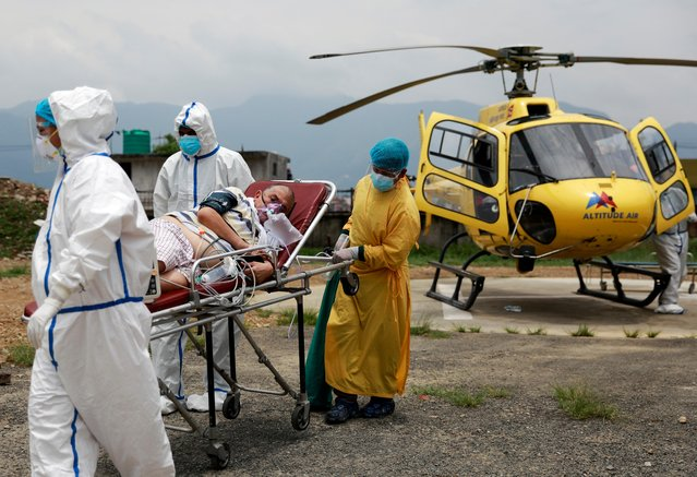 Health workers carry Ramjee Kunwar, 65, a COVID-19 patient from a helicopter to an ambulance after being airlifted from Pokhara to Kathmandu due to health complications, amid the spread of coronavirus disease (COVID-19), in Kathmandu, Nepal on May 30, 2021. (Photo by Navesh Chitrakar/Reuters)