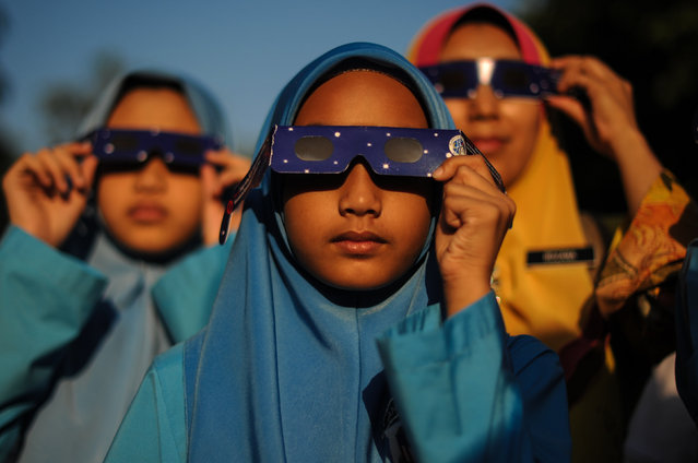 Malaysian school children wearing glasses with special filters watch the partial solar esclipse at the National Planetarium in Kuala Lumpur on March 9, 2016. A total solar eclipse swept across the vast Indonesian archipelago on March 9, witnessed by tens of thousands of sky gazers and marked by parties, Muslim prayers and tribal rituals. Partial eclipses were also visible over other parts of Asia and Australia. (Photo by Mohd Rasfan/AFP Photo)