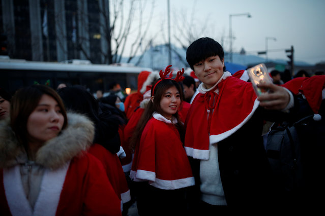 A couple dressed in Santa costume takes a selfie during a protest demanding South Korean President Park Geun-hye's resignation in Seoul, South Korea, December 24, 2016. (Photo by Kim Hong-Ji/Reuters)