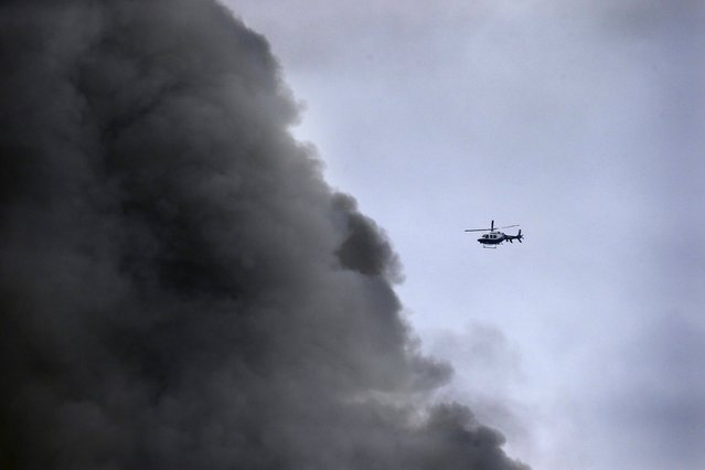 A New York City Police helicopter flies near billowing smoke above the site of a residential apartment building collapse and fire in New York City's East Village neighborhood March 26, 2015. (Photo by Brendan McDermid/Reuters)