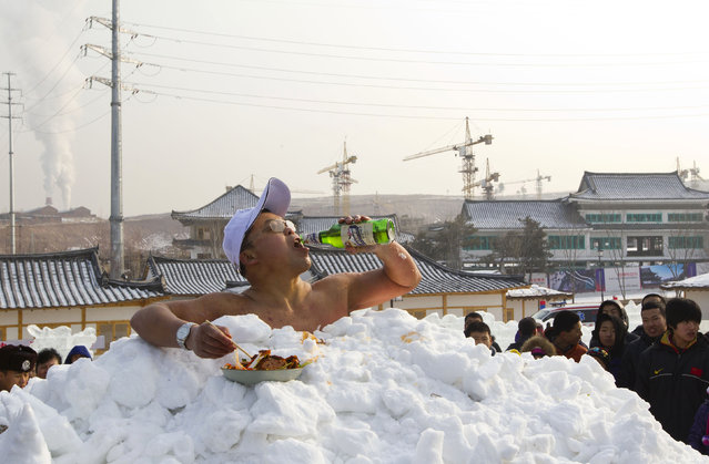Jin Songhao drinks beer as he sits in snow during a cold endurance performance in Yanji, Jilin province, January 12, 2013. Jin set the Guinness record for the longest time spent in direct full body contact with snow on January 17, 2011 with a time of 46 minutes and seven seconds, local media reported. (Photo by Reuters/Stringer)