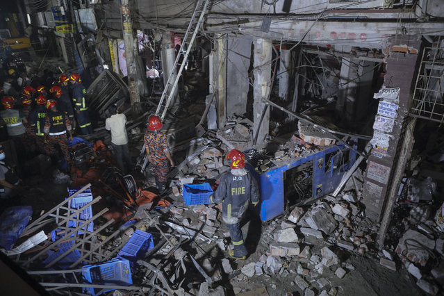 Rescuers stand amid the debris after a blast at a market in Dhaka, Bangladesh, Sunday, June 27, 2021. (Photo by AP Photo/Stringer)