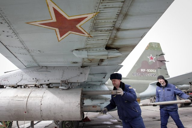 Servicemen load air-to-ground missiles onto a Sukhoi Su-25 jet fighter during a drill at the Russian southern Stavropol region, March 12, 2015. Russia has started military exercises in the country's south, as well as in Georgia's breakaway regions of South Ossetia and Abkhazia and in Crimea, annexed from Ukraine last year, news agency RIA reported on Thursday, citing Russia's Defence Ministry. (Photo by Eduard Korniyenko/Reuters)