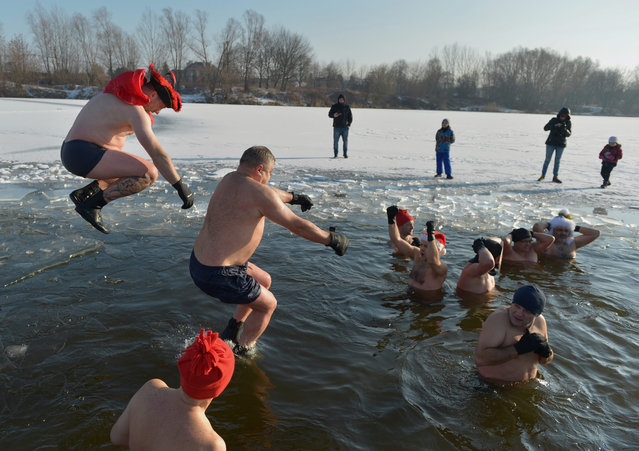 """embers of the Ice Swimming Club """"Icicle"""" jump into the ice cold water during the traditional New Year's Day plunge in municipal swimming zone in former gravel pit in Rzeszow, Poland, 01 January 2017. (Photo by Darek Delmanowicz/EPA)"""
