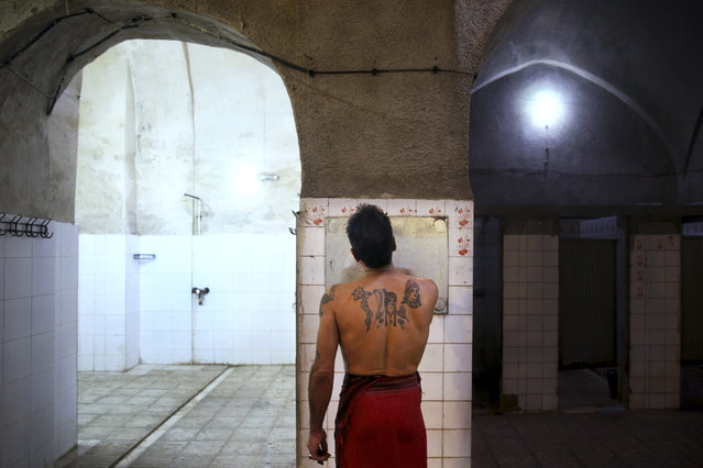 In this January 9, 2015 photo, a man with Persian tattoos shaves at the Ghebleh public bathhouse, in Tehran, Iran. (Photo by Ebrahim Noroozi/AP Photo)