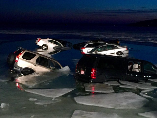 Multiple vehicles are submerged after falling into the ice on Geneva Lake in Lake Geneva, Wis., on Satrurday, February 6, 2016. The cars were parked on the ice of the lake when they began breaking through Saturday. Officers arrived and found 15 vehicles were partially submerged in the water. No one was hurt. (Photo by Daniel Gaitan/The Kenosha News via AP Photo)