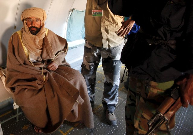 Saif al-Islam Gaddafi, son of late Libyan leader Muammar Gaddafi, sits in a plane after being captured by rebels, November 19, 2011. (Photo by Ismail Zitouny/Reuters)