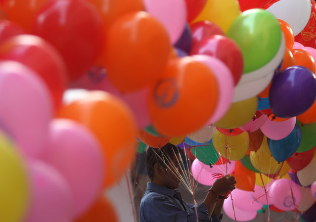 A man prepares balloon before a ceremony at the headquarters of the Cambodian People's Party (CPP) to mark the 38th anniversary of the toppling of Pol Pot's Khmer Rouge regime in Phnom Penh, January 7, 2017. (Photo by Samrang Pring/Reuters)