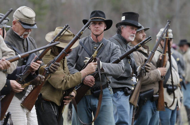 Confederate re-enactors check their weapons during a re-enactment of the Battle of Appomattox Station, Wednesday, April 8, 2015, as part of the 150th anniversary of the surrender of the Army of Northern Virginia to Union forces at Appomattox Court House, in Appomattox, Va. (Photo by Steve Helber/AP Photo)
