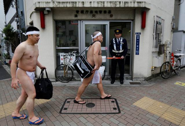 Man wearing loin cloths walk past a police box after they bathe in ice-cold water outside the Teppozu Inari shrine in Tokyo, Japan, January 8, 2017. (Photo by Toru Hanai/Reuters)