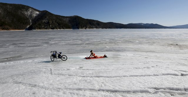A woman enjoys the sun on the bank of the Yenisei River, with the air temperature at about 13 Celsius (55.4 degrees Fahrenheit), in the Taiga district outside Russia's Siberian city of Krasnoyarsk April 6, 2015. (Photo by Ilya Naymushin/Reuters)