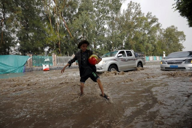 A Yemeni boy wades and attempts to traverse a flooded street following heavy rainfall in Sana'a, Yemen, 23 July 2021. Heavy rainfall and associated floods have hit several cities of Yemen over the past few days. (Photo by Yahya Arhab/EPA/EFE)