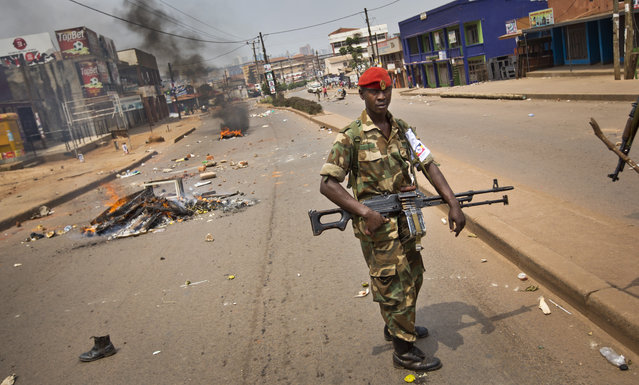 A heavily armed military policeman patrols next to burning barricades set up by angry supporters of opposition leader Kizza Besigye, near to his party headquarters, in Kampala, Uganda, Friday, February 19, 2016. Police in Uganda arrested opposition leader Kizza Besigye at his party's headquarters Friday after heavily armed police surrounded the building and fired tear gas and stun grenades at his supporters who took to the streets. (Photo by Ben Curtis/AP Photo)