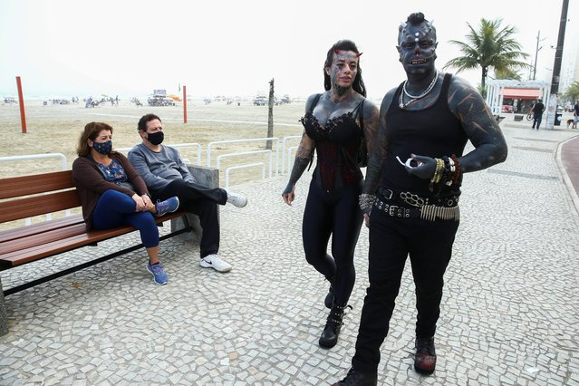 """Brazilian tattoo artist Michel Praddo, also known as Diabao or Human Satan, and his wife Carol Praddo, known as Mulher Demonia or Demon Woman, walk as people observe them at the beach shore in Praia Grande, Brazil on August 18, 2021. """"Turning into the devil wasn't something I planned, it was not my idea"""", said Prado. """"The sinister attracted me"""". Once homeless and a drug addict, the 46-year-old tattoo artist said those tough years helped make him a better man who is constantly working towards self-knowledge. (Photo by Carla Carniel/Reuters)"""