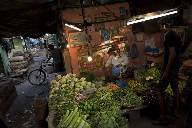A man buys vegetables from a wayside vendor in the morning in the old Delhi area of New Delhi, India, Tuesday, April 14, 2015. The four-century-old neighborhood is chaotic and crowded, yet is the vibrant heart of the city. (Photo by Bernat Armangue/AP Photo)