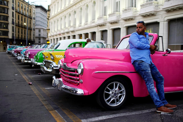 Driver Giovani Bernati waits for tourists beside vintage cars used as taxi in Havana, Cuba, October 5, 2018. Picture taken October 5, 2018. (Photo by Alexandre Meneghini/Reuters)