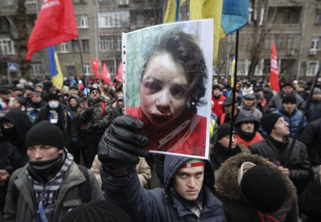 A protester holds a picture of journalist Tetyana Chornovil, who was beaten and left in a ditch just hours after publishing an article on the assets of top government officials, during a protest rally in front of the Ukrainian Ministry of Internal Affairs in Kiev December 25, 2013. Chornovil, a prominent activist who has given speeches at recent anti-government protests, told police her car was stopped by a vehicle just after midnight. (Photo by Reuters/Stringer)