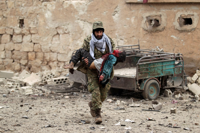 A rebel fighter carries an injured boy after a car bomb explosion in Jub al Barazi east of the northern Syrian town of al-Bab, Syria January 15, 2017. (Photo by Khalil Ashawi/Reuters)