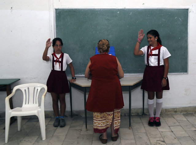 School children salute as a woman casts her ballot during Cuba's municipal elections at a polling station in Havana, Cuba, Sunday, April 19, 2015. (Photo by Desmond Boylan/AP Photo)