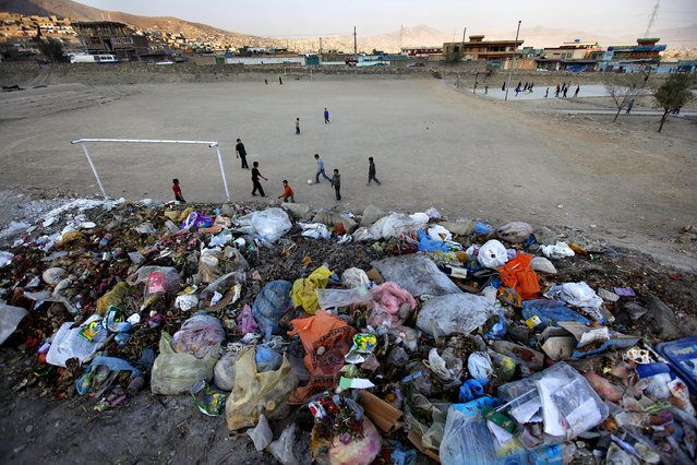 Afghan boys play soccer along a road in Kabul, November 16, 2009. (Photo by Jerry Lampen/Reuters)