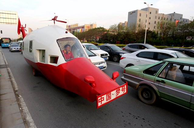"Yuan Jingying, drives his home-made vehicle in the shape of helicopter along a road in Zhengzhou, Henan province, April 21, 2015.  Yuan, a retired engineer, spent five years making the 12.5-metre-long, 2.8-metre-high vehicle and hopes to drive his mother around China with his ""helicopter"" someday, according to local media. (Photo by Reuters/China Daily)"