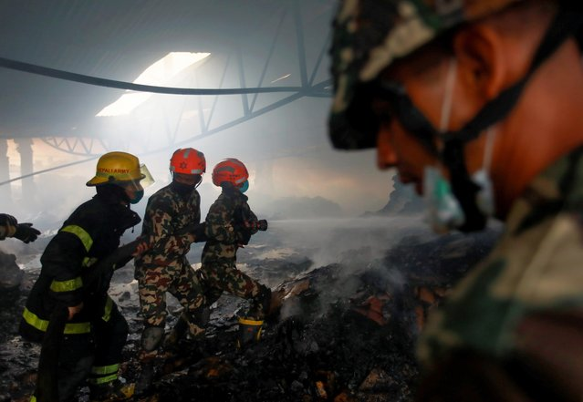Firefighters work to douse a fire at a Nebico Biscuit Factory inside Balaju Industrial area in Kathmandu, Nepal on August 7, 2021. (Photo by Navesh Chitrakar/Reuters)