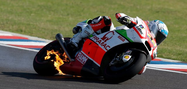 Pramac Ducati Racing rider Yonny Hernandez of Colombia rides his motorcycle as fire is seen on it during Argentina's MotoGP Grand Prix at the Termas de Rio Hondo International circuit in Termas de Rio Hondo, April 19, 2015. (Photo by Marcos Brindicci/Reuters)