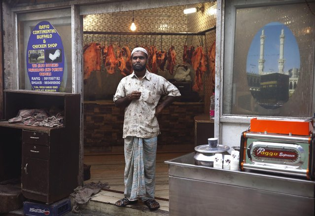 In this April 7, 2015 photo, a butcher stands outside his shop in New Delhi, India. As a resurgent Hindu majority pushes for a nationwide ban on slaughtering cows, seen as sacred, the meat industry is scrambling to survive and come up with a way to continue providing beef to the hundreds of millions within the country who still eat it despite the religious taboo. (Photo by Manish Swarup/AP Photo)
