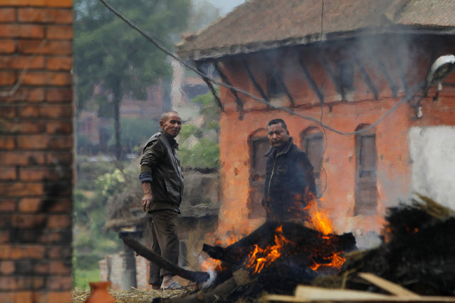 Nepalese people stand beside the funeral pyre of a family member who died in Saturday's earthquake in Bhaktapur, Nepal, Sunday, April 26, 2015. (Photo by Niranjan Shrestha/AP Photo)