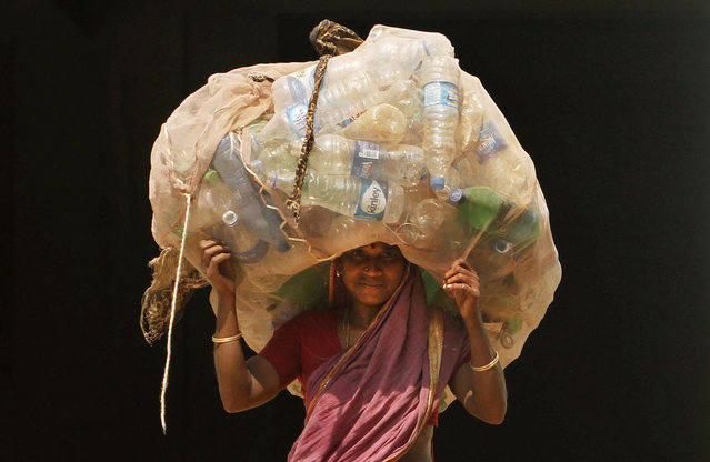 An Indian woman carries a sack of used plastic bottles to be sold at a recycled plant on the International Woman's Day in the eastern Indian city of Bhubaneswar, India, Tuesday, March 8, 2016. (Photo by Biswaranjan Rout/AP Photo)