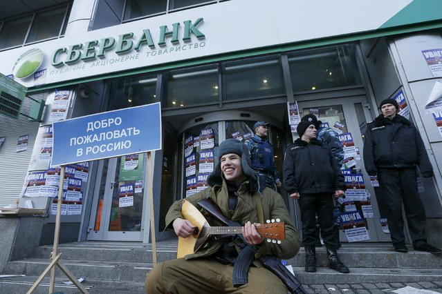 """A member of the Azov civil corp sits next to a placard reading, """"Welcome back to Russia"""" during a protest in front of a branch of Sberbank, which protesters say supports Russian """"aggression"""" in Eastern Ukraine, in Kiev, Ukraine January 30, 2017. (Photo by Valentyn Ogirenko/Reuters)"""