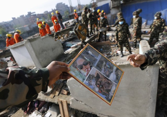 A Nepal army soldier hands over a photo frame to another after collecting it from the rubble of a destroyed house, after the April 25 earthquake, in Kathmandu, Nepal April 29, 2015. (Photo by Adnan Abidi/Reuters)