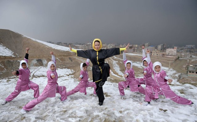 In this photograph taken on January 29, 2017, Afghan members of a wushu martial arts group led by trainer Sima Azimi (C), 20, pose for a photograph at the Shahrak Haji Nabi hilltop overlooking Kabul. Afghanistan's first female wushu trainer, Sima Azimi, 20, is training 20 Afghan girls aged between 14 – 20 at a wushu club in Kabul, after learning the sport while living as a refugee in Iran. (Photo by Wakil Kohsar/AFP Photo)