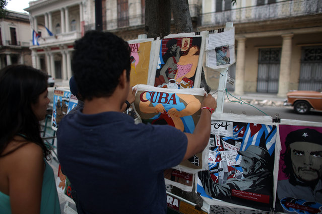 Tourists from Colombia look at posters in a street arts fair in Havana, February 20, 2016. (Photo by Alexandre Meneghini/Reuters)