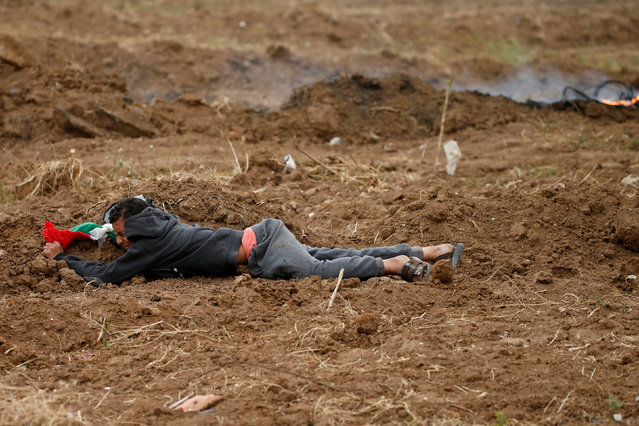 A demonstrator with a Palestinian flag takes cover from Israeli gunfire and tear gas during a protest marking Land Day and the first anniversary of a surge of border protests, at the Israel-Gaza border fence east of Gaza City March 30, 2019. (Photo by Mohammed Salem/Reuters)